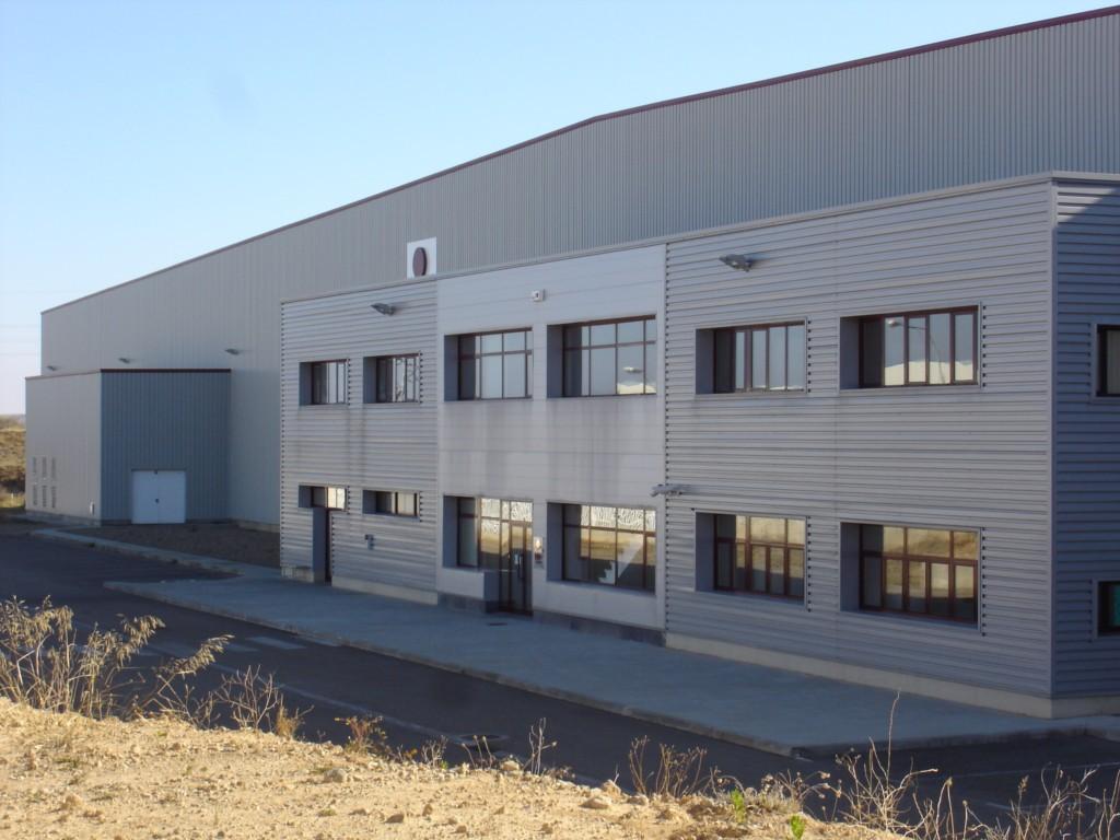 Nave industrial de grandes luces con núcleo de oficinas